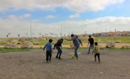أطفال عرب الكعابنة يلهون كرم القدم في خلفية الصورة مستوطنة ادم